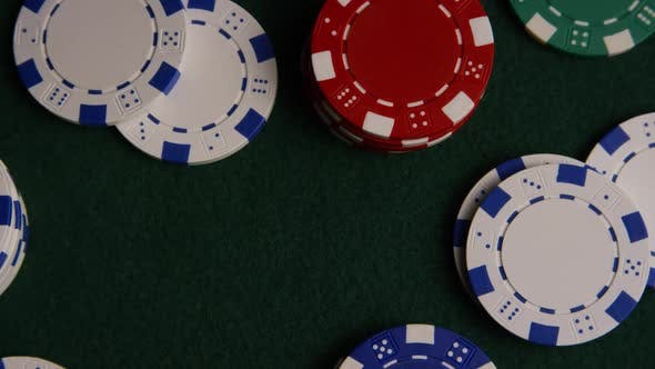 Rotating shot of poker cards and poker chips on a green felt surface - POKER 029