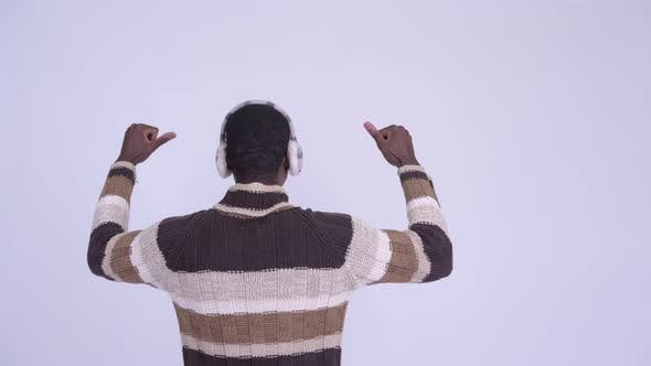 Cover Image for Rear View of Young Happy African Man with Fists Raised Ready for Winter