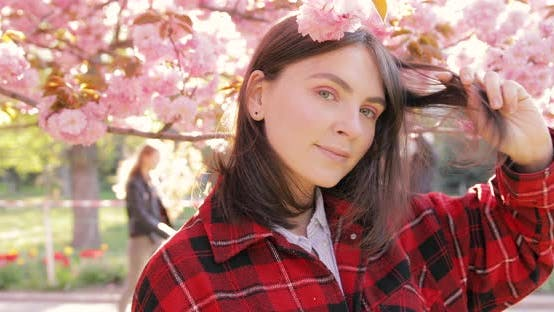 Thumbnail for Portrait of beautiful European young woman in red jacket with pink cherry blossoms background