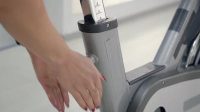 Woman Adjusting the Seat on Her Spin Bike