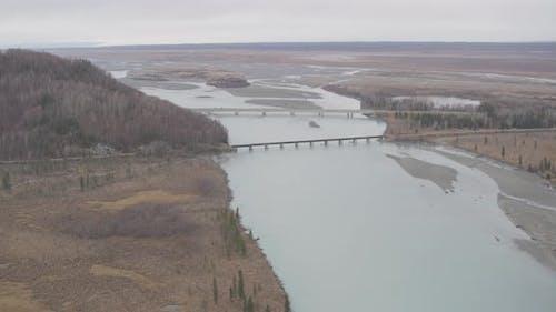 Luftaufnahme des Hubschraubers Alaskan Highway entlang des Flusses, über Eisenbahnbrücke und Überführung, Drohne