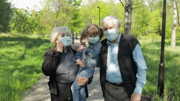 Großeltern mit Enkelin zieht Masken nach Coronavirus-Quarantäne Ende