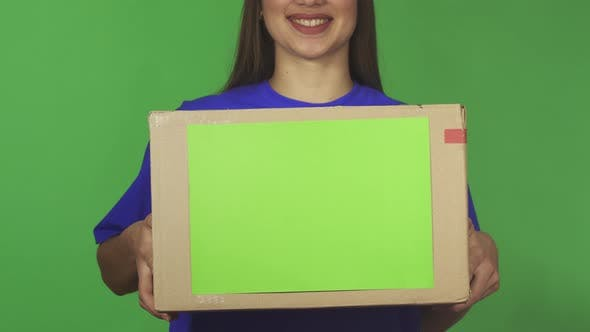 Thumbnail for Cropped Shot of a Delivery Woman Smiling Holding Carboard Box with Copyspace