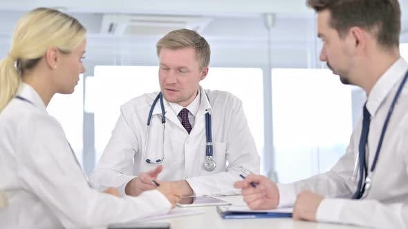 Thumbnail for Focused Young Doctor Taking Notes and Listening To Senior Doctor