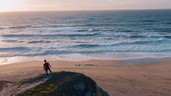 Fit Man is Standing On The Edge of the Cliff