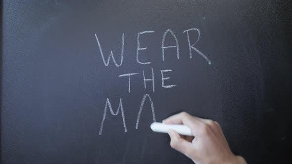 Hand writes Wear the mask on chalkboard.