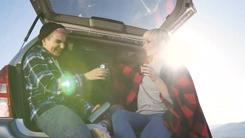 Adventurous Young Women Sitting in the Car Trunk, Holding Thermos and Drinking Coffee
