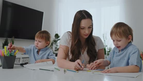 Cover Image for A Young Mother with Two Children Sitting at a White Table Draws Colored Pencils on Paper