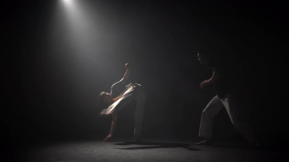 Thumbnail for Handsome Males Practicing Capoeira in Darkness Against Spotlight in Studio