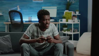 Happy Man Playing Video Games with Controller on Console