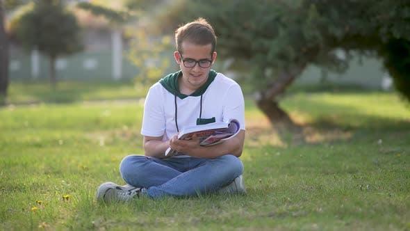 University student sitting on grass, writing essay, literary studies project