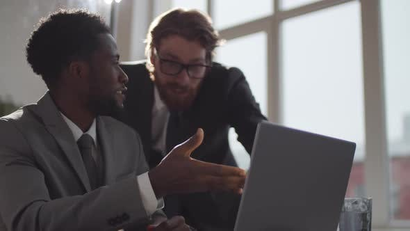 Thumbnail for Two Diverse Coworkers Using laptop and Celebrating Business Success