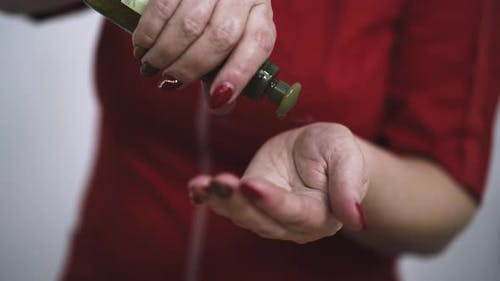 Woman Massage Therapist Applies Oil Onto Palms in Clinic
