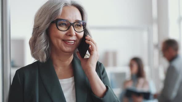 Thumbnail for Beautiful Senior Business Lady Speaking on Mobile Phone in Office
