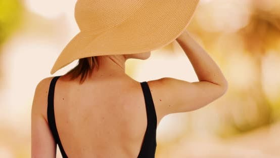 Thumbnail for Rear view of woman in floppy sunhat on soft golden yellow bokeh background