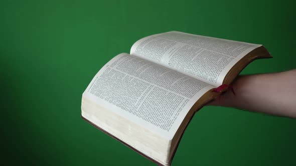 Man Holding Open Bible In His Hands Isolated On Chroma Key Green Screen Background