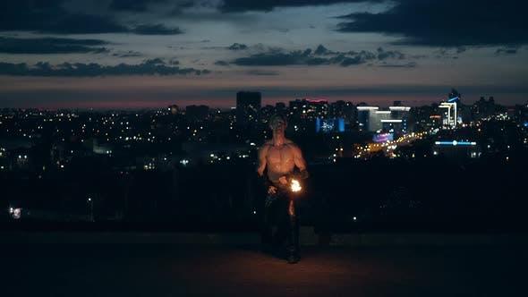 Jeune homme blond fait des tours avec le feu, les genoux mâles tout en respirant le feu faisant boule de feu