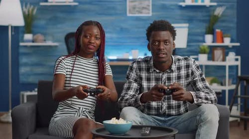 African American People Playing Video Game with Joysticks