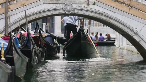 Thumbnail for Several gondolas carrying tourists along narrow channel with bridge, boats aside
