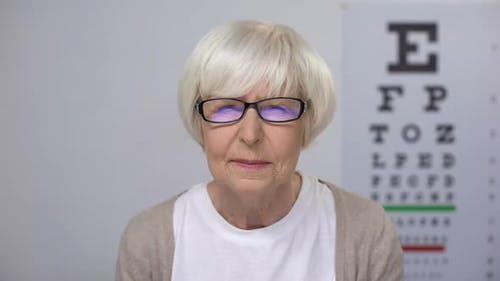 Elderly Woman Upset With Sight Examination Taking Off Spectacles, Cataract Risk