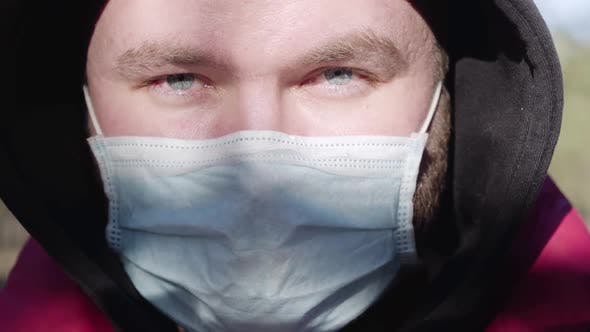 Thumbnail for Extreme Close-up Face of Young Caucasian Man in Face Mask on Sunny Day Outdoors. Portrait of