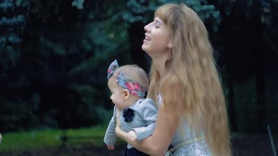 Young Girl is Playing with a Young Baby