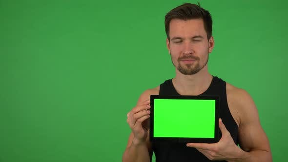 Thumbnail for A Young Handsome Athlete Shows a Tablet with Green Screen To the Camera - Green Screen Studio
