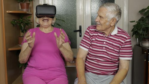 Grandfather and Grandmother with VR Headset Helmet Play Games, Watch Virtual Reality 3D 360 Video