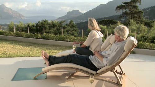 Mature couple on sunloungers looking at view