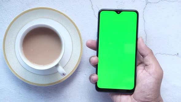 Blick aus der Vogelperspektive auf die Hand der Person mit Smartphone und Kaffeetrinken