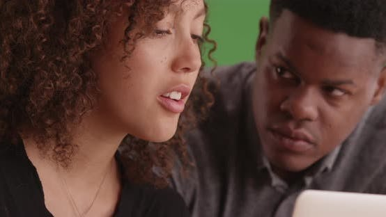 Thumbnail for Two young black business workers using a laptop on green screen
