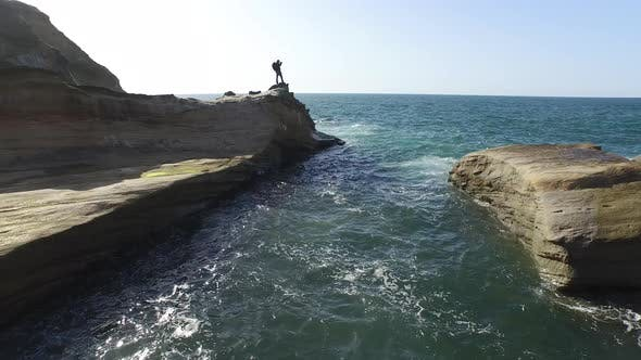 Thumbnail for Aerial shot of backpacker standing on rock overlooking Pacific Ocean