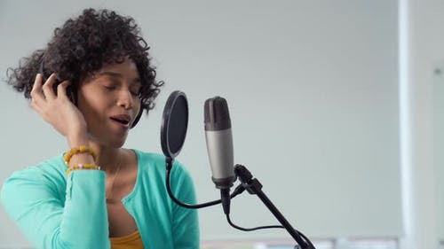 Young African American Pretty Woman Singing in Front of Microphone