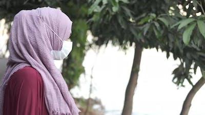Thoughtful Muslim Woman with Flu Mask Looking Away