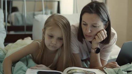 Mutter und Tochter lesen ein Buch im Bett
