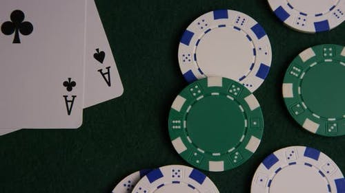 Rotating shot of poker cards and poker chips on a green felt surface - POKER 043