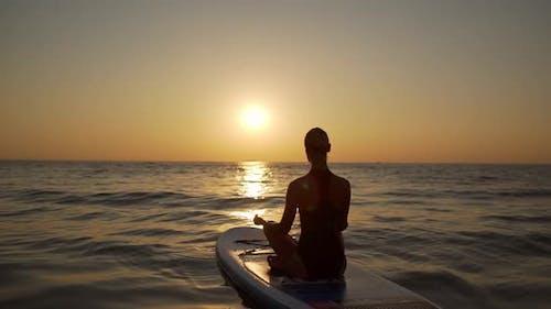 Young Woman Meditates Sitting in Yoga Asana on Supboard