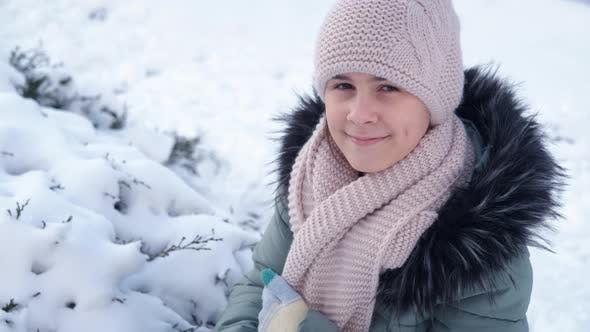Teen by the snowy tree.