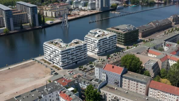Forwards and Tilt Up Reveal of Molecule Man Sculpture on Spree River and Large City Panorama