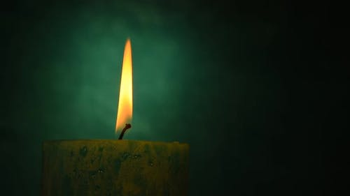 Teal candle trembling flame out of the dark and blown out