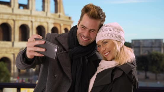 Thumbnail for Attractive tourist couple take a selfie smiling by the Coliseum
