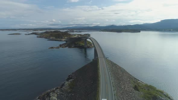 Cover Image for Car with Motorhome Travels on Storseisundet Bridge. Atlantic Ocean Road in Norway. Aerial View