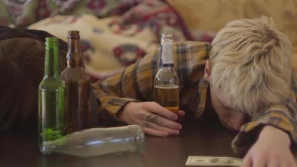 Cover Image for Young Bad Looking Friends Lying on the Table Near Empty Alcohol Bottles