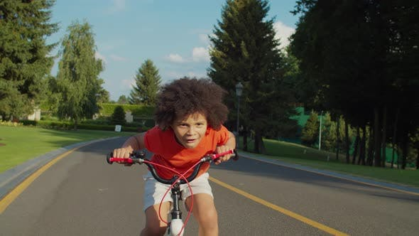 Thumbnail for Excited Little Boy Riding Bicycle in Public Park