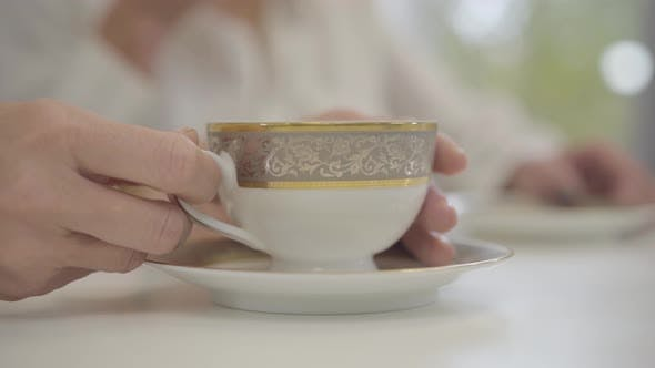 Thumbnail for Close-up of Adult Female Caucasian Hand Taking the Cup with Tea or Coffee and Putting It Back on the