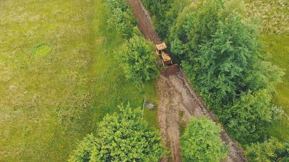 Thumbnail for Aerial View Bulldozer Levels and Repairs a Road in the Mountains. The Bulldozer Moves Slowly and