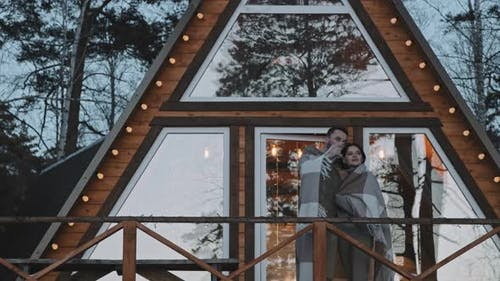 Couple Standing on Porch of A-Frame Cabin
