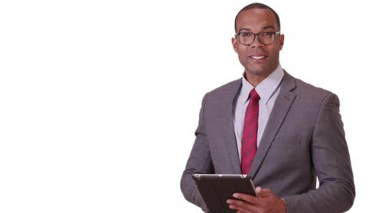 Thumbnail for A black business professional poses for a portrait with his tablet and glasses on a white background