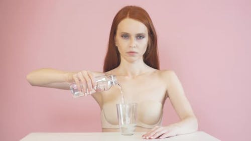 Exhausted Red-haired Girl Pours Water Into a Glass. Diet. Anorexia