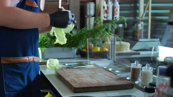 Cuisine, Male Chef in Gloves Prepares Vegetables on a Cutting Board for Preparing Salad in the